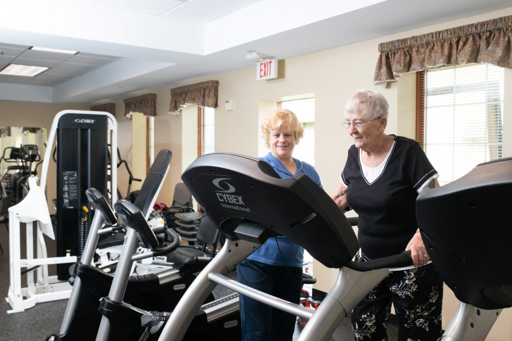 Avila's Fitness Rehab Specialist working with a resident in the fitness center