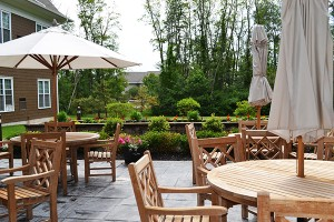Avila Lodge outdoor patio with chairs and umbrella and gardens in background