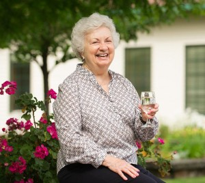 resident with glass of wine in garden