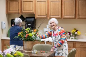 smiling resident arranging flowers in case