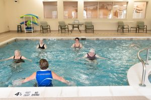 residents on hydroriders in pool with trainer in pool