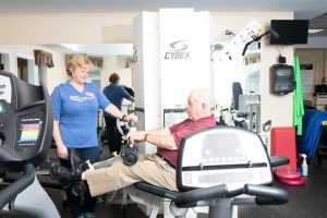 resident exercising on equipment with rehab specialist assiting
