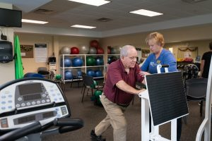rehab specialist working with senior in fitness room
