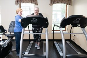 rehab specialist with resident on treadmill