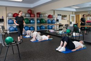 resident and trainer doing floor stretching exerciseson mats
