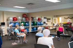 residents with trainer in chair exercise class