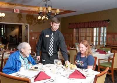 resident and family being served lunch by waiter