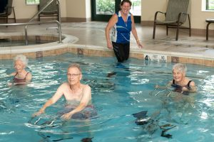 residents smiling with trainer on hydroriders in pool