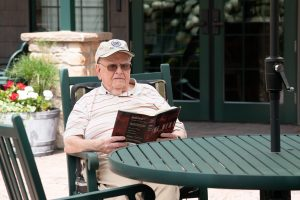 senior resident with baseball cap reading book on the patio