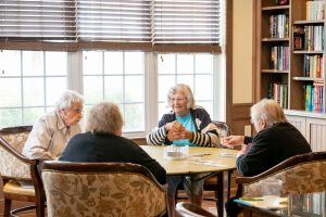 4 ladies playing cards in the library