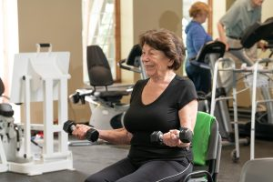 resident doing chair exercises with hand weights