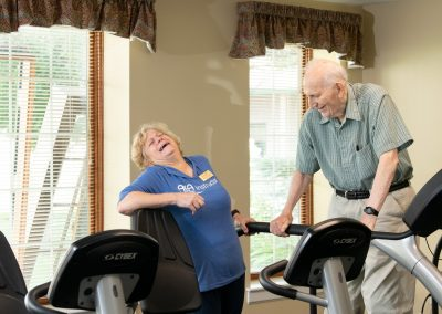 fitness specialist with resident on treadmill