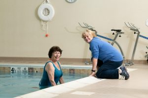 rehab specialist with resident talking at the pool