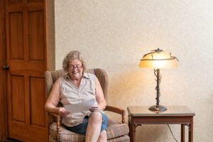 avila resident reading in a sitting chair with lighted lamp