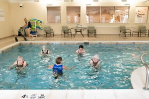 residents exercising in pool on hydro riders