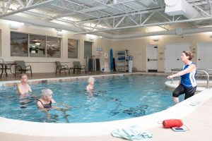 Senior residents exercising on hydroriders in pool