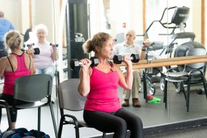 trainer with residents lifting weights