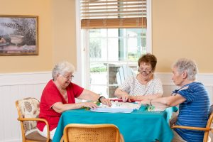 Three ladies playing game at table