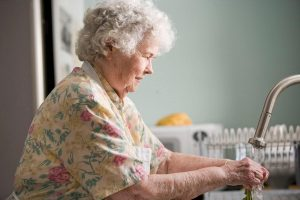 older woman washing hands