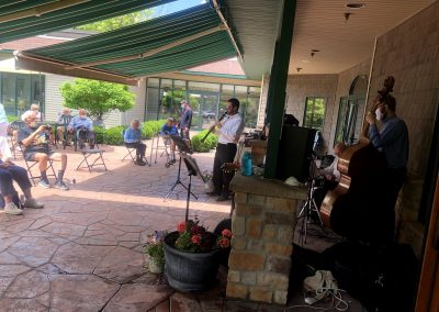 Retirees enjoying live entertainment outside practicing social distancing